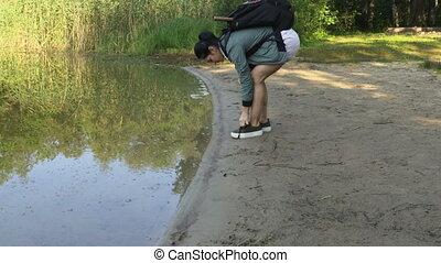 Woman hiker take off sneakers near lake