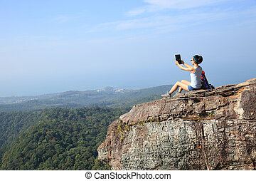 woman hiker taking photo with digital tablet at mountain peak