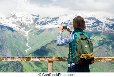 Woman hiker taking photo with smartphone at mountain. Backpacker photos landscape on the mobile phone.
