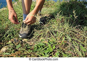 woman hiker tying shoelace on seaside mountain peak