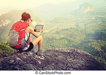 woman hiker use digital tablet at mountain peak cliff