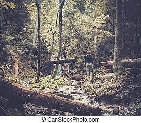 Woman hiker walking across river in a forest