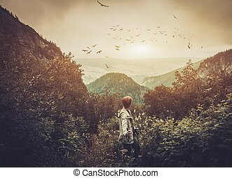 Woman hiker walking in a mountain forest