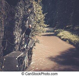 Woman hiker walking near river in a Slovenky Ray, Slovakia
