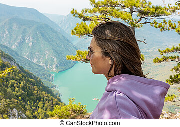Woman hiker wearing sunglasses at mountain viewpoint and enjoying the view of a lake and canyon