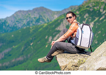 woman hiker with a backpack in the mountains sits on a rock