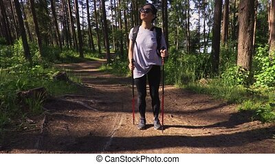 Woman hiker with backpack and Nordic poles in forest on path