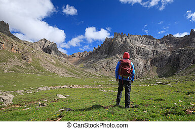 woman hiker with backpack hiking at high altitude mountains