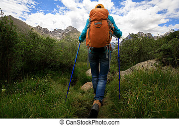 woman hiker with backpack hiking in the nature