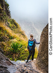 Woman hiker with backpack in rocky terrain on a narrow trail to Coculi. Santo Antao, Cabo Verde