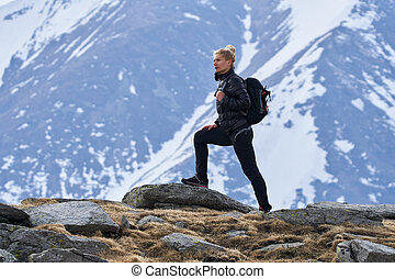 Woman hiker with backpack in the mountains