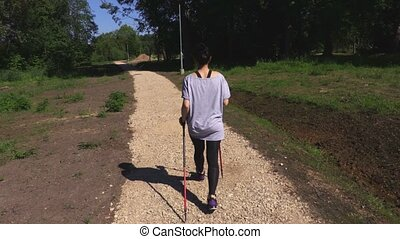 Woman hiker with Nordic walking poles on path in the park
