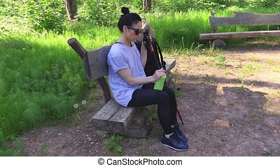 Woman hiker with Nordic walking poles relaxing on bench