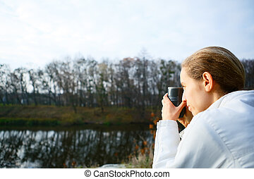 Woman hiker with thermo cup of tea in hand on the autumn nature