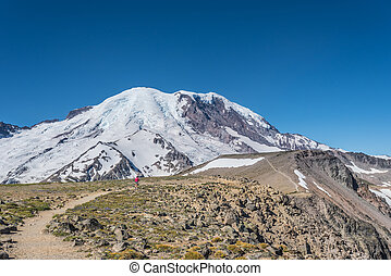 Woman Hikes Burroughs Mountain Trail underneath Mount Rainier