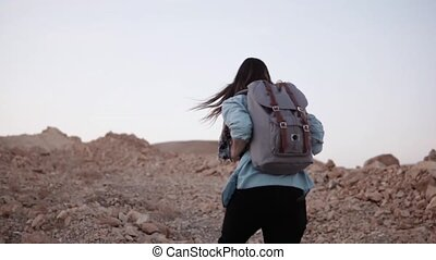 Woman hikes up on a steep rocky hill. Slow motion. Tourist...