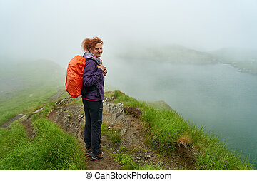 Woman hiking by a lake in the mountains