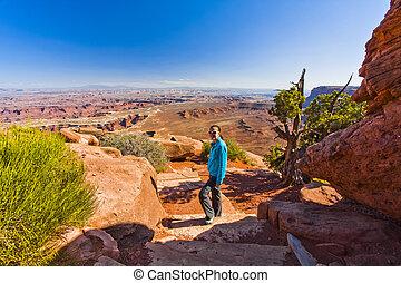Woman Hiking in Canyonland's Desert Terrain
