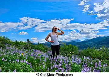 Woman hiking in meadows in bloom.