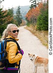 Woman hiking in mountains with akita dog