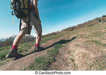 Woman hiking in the mountain, body part close up, one person walking in the Alps, backpacking summer adventure travel, rear view, toned image
