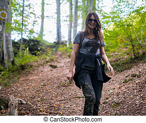 Woman hiking on a trail in the woods
