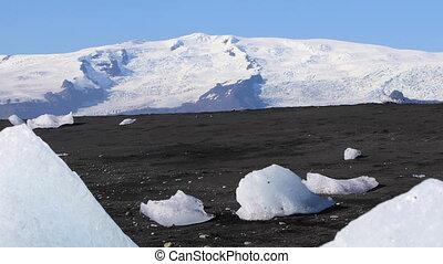 Woman hiking on black sand iceberg beach - Woman wearing...