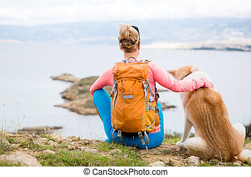 Woman hiking walking with dog on sea landscape
