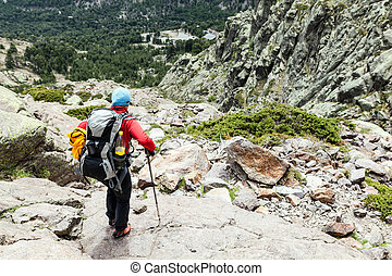 Woman hiking with backpack in Corsica mountains