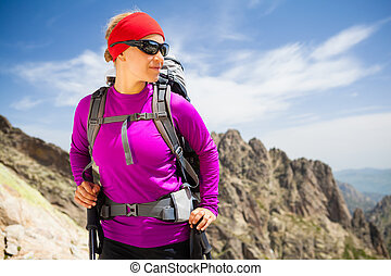 Woman hiking with backpack in inspirational mountains