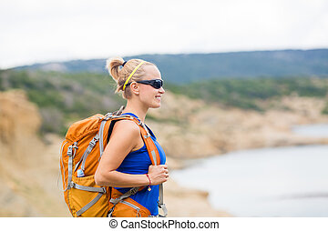 Woman hiking with backpack in mountains at seaside
