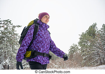 Woman Hiking with Big Backpack in Beautiful Winter Forest