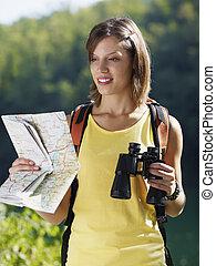 woman hiking with binoculars and map