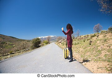 woman hitch-hiking on the road
