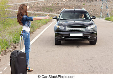 Woman hitchhiking after a breakdown with her car