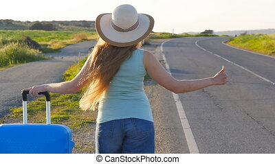 Woman hitchhiking by the roadside - Girl hitchhiking by the ...