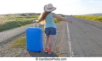 Woman hitchhiking by the roadside - Girl hitchhiking by the...