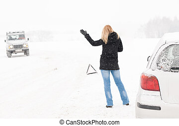 Woman hitchhiking having trouble with car snow