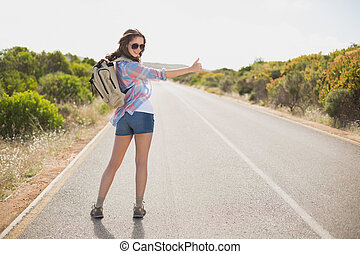 Woman hitchhiking on countryside road - Portrait of a pretty...