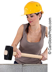 Woman hitting wall with sledge-hammer