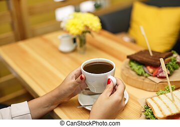 woman hold a cup of coffee at backgroud wooden table, on which lies a sandwich