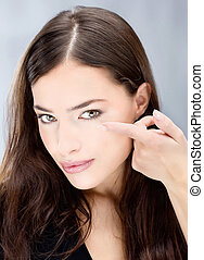 Woman hold contact lens in front of eye
