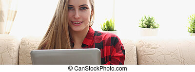 woman hold laptop in arms sit on sofa