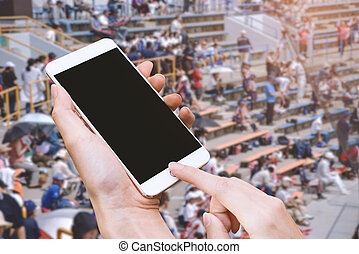 Woman hold smart phone and touch button by hand with blank screen for advertisement, Stadium and audiences background ,Technology and Sport concept