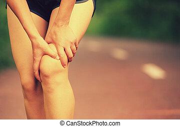 woman hold sports injured leg