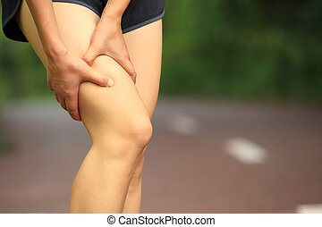 woman hold sports injured leg - woman runner hold her sports...