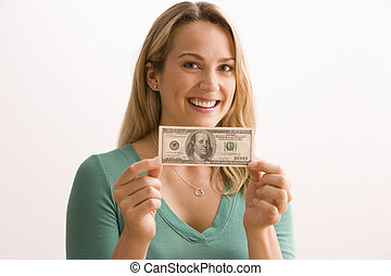 An attractive young woman is holding up a $100.00 bill and smiling at the camera. Horizontal shot.