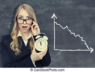 Woman holding a alarmclock. blackboard background with diagram.