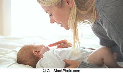 Woman holding a baby who lying on a bed