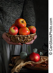woman holding a basket of apples
